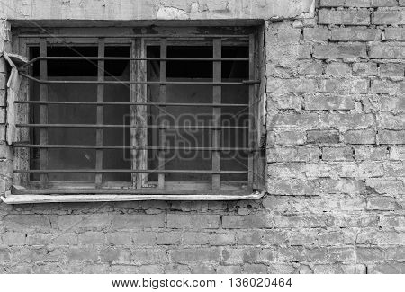 old window closeup with a rusty lattice on an ancient brick wall of monochrome tone and a blank space
