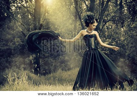 Magnificent brunette woman wearing long black dress walking in a mystic forest. The old times, the G