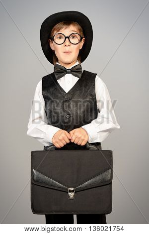 Portrait of the old styled boy in elegant suit and bowler hat with his suitcase. Studio shot. Kid's fashion.