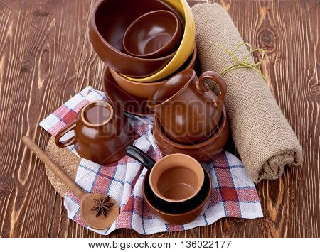 Stack of crockery on wooden table with anise and linen dish-cloth. Set of pottery kitchenware. Buffet, restaurant equipment. Empty plates and cups.