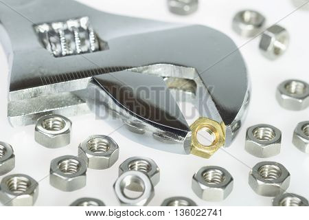 Golden screw nut surrounded by steel screw nuts with adjustable wrench. Stand out from the crowd concept.