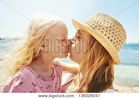 Young Mother And Her Daughter Kissing At The Beach