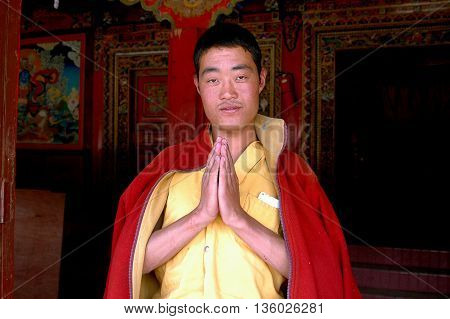 Gamel China - August 24 2006: Tibetan monk with clasped hands welcomes visitors to the Gamel Chador Gonchen Temple