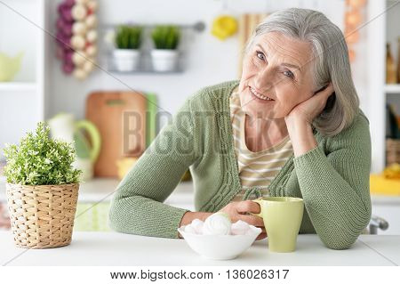 happy Senior woman portrait at table with tea cup