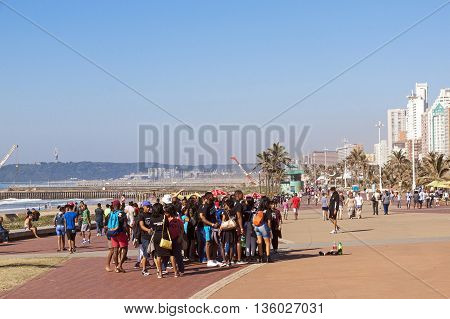 People Walking Along  Promenade On Beach Front 2