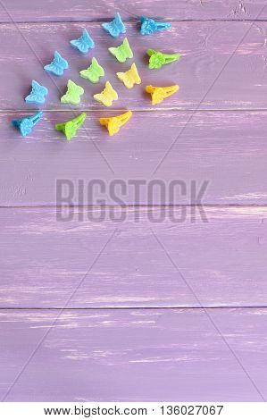 Bright hair clips with flowers and butterflies. Kit of colorful hair clips for girls on lilac wooden background with copy space for text. Vertical photo. Top view