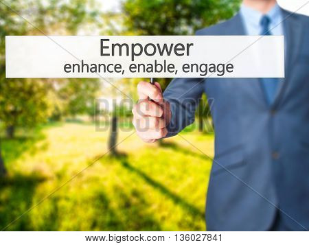 Empower Enhance, Enable, Engage - Businessman Hand Holding Sign