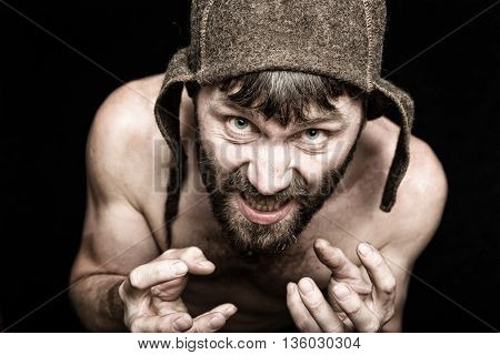 Dark portrait of scary evil sinister bearded man with smirk, makes various hand's signs and expresses different emotions. strange Russian man with a naked torso and a woolen hat.