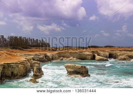 maritime landscape - turquoise sea with waves and rocks on background of cloudy sky. Cliffs at water. The Mediterranean coast near Paphos Cyprus