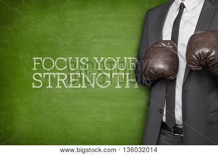 Focus your strenght on blackboard with businessman wearing boxing gloves