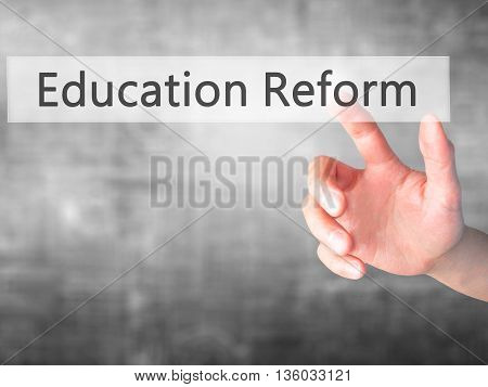 Education Reform - Hand Pressing A Button On Blurred Background Concept On Visual Screen.