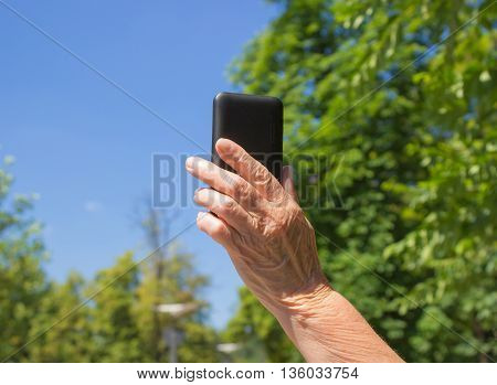 The phone in old female hand on the blue sky background