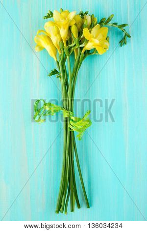 Bouquet of freesia flowers lying on the wooden background