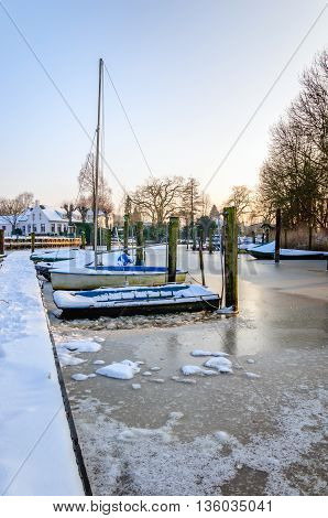 Small boats frozen in the ice of a little harbor in a Dutch village in the winter season.