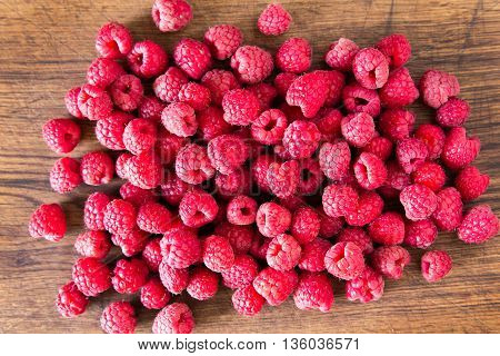 Ripe sweet raspberries in bowl on wooden table. Close up, top view, high resolution product