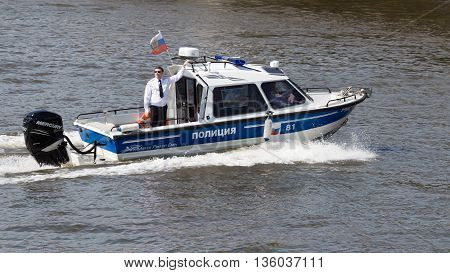 Moscow - May 9 2016: Police Boat with the police in black glasses and on board the Russian flag patrol the territory of the Moscow River during the Victory parade on May 9th