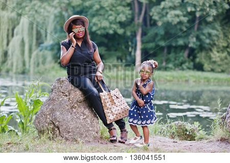Stylish African American Mother And Daughter At Sunglasses. Black Woman With Mobile Phone