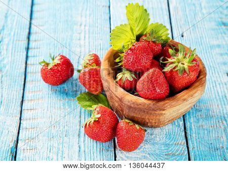 Fresh strawberry pile in bowl with leaves placed on old wooden planks