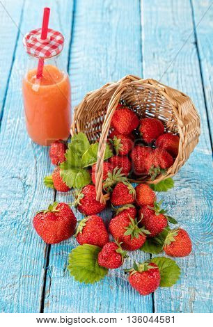 Fresh strawberry pile in basket with fresh juice placed on old wooden planks