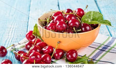 Fresh cherry pile in bowl with leaves placed on old wooden planks