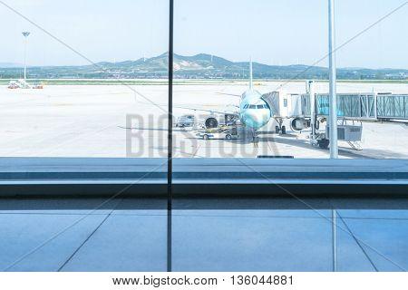 airplane on airfield through glass window