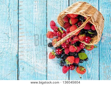 Fresh berry fruit pile in basket with leaves placed on old wooden planks. Shot from aerial view, copyspace for text