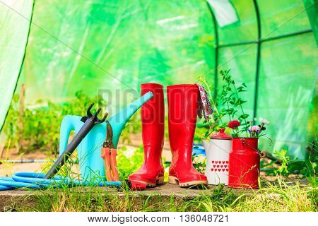 Gardening tools outdoor in garden red rubber boots water can blue hose greenhouse in the background