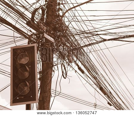 Tangled and messy electrical cables and wires on electric pole in front of the traffic lights. Sepia color tone.