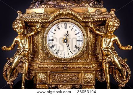 Ancient bronze table clock - gilded bronze and marble. On a black background. Detail