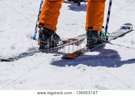 Man legs wear snowshoes and orange trousers stand on snow Skiing equipment and extreme winter sports at place for skiing