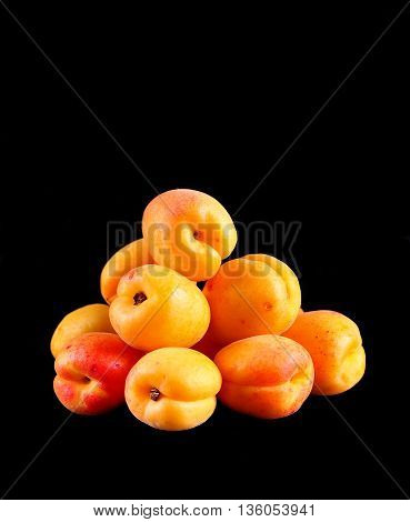 Organic apricots in a copper plate on a black background.