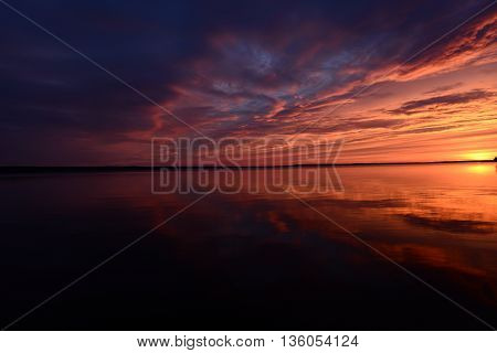 Sunset sky reflected on lake water surface