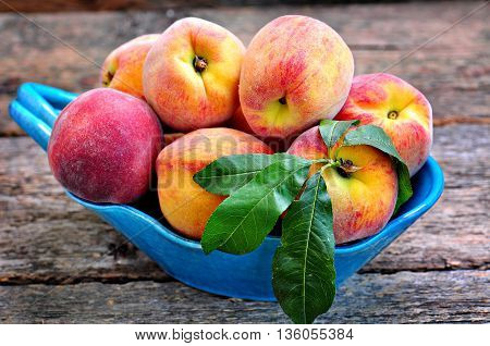 Fresh organic peaches on a wooden background