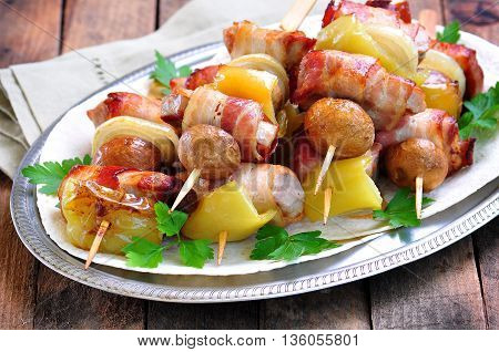 Pork wrapped in bacon on skewers grilled with onions, mushrooms and peppers.