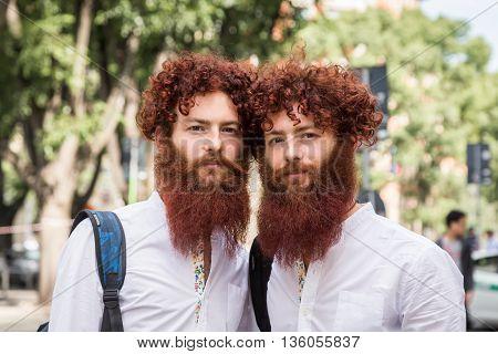 MILAN ITALY - JUNE 21: Fashionable bearded twins pose outside Armani fashion show building during Milan Men's Fashion Week on JUNE 21 2016 in Milan.