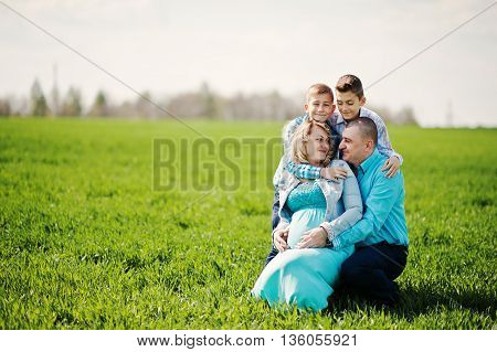 Happy Pregnant Family With Two Sons, Dressed In A Turquoise Clothes, Spending Time Together At Green