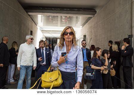 MILAN ITALY - JUNE 21: Fashionable people gather outside Armani fashion show building during Milan Men's Fashion Week on JUNE 21 2016 in Milan.