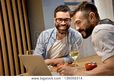 Trendy guys in bar connected with laptop