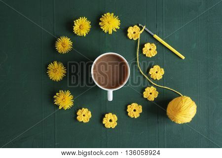 A circle of dandelions, crocheted flowers and a cup of coffee on green background.