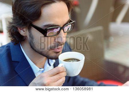 Man serious drinking coffee business eyeglasses suit sitting restaurant