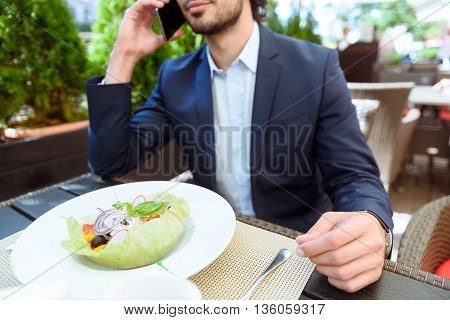 Busy young man is using mobile phone for communication. He is eating salad in restaurant