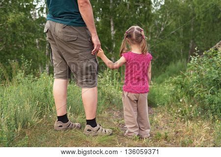 Father and daughter walking on a hill. They are standing backward to the camera looking at something.