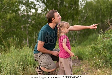 Father and daughter walking on a hill. He is pointing at something. They both are looking that way.
