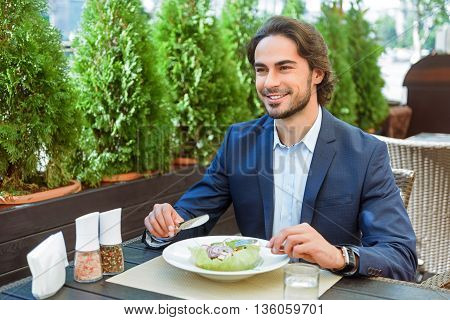 Happy young businessman is having breakfast in cafe. He is sitting at table and smiling