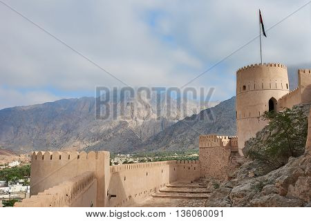 Watch tower of an ancient fort in oman against the backdrop of a blue sky