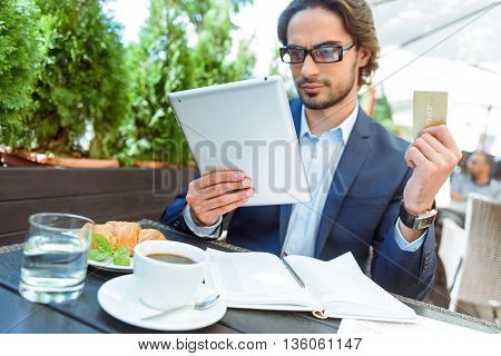 Successful young businessman is waiting for waiter in cafe. He is looking at the tablet with concentration. Worker is sitting and holding a credit card