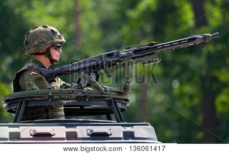 BURG / GERMANY - JUNE 25 2016: german soldier secures with machine gun a zone on open day in barrack burg / germany at june 25 2016