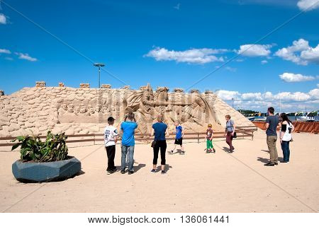 LAPPEENRANTA, FINLAND - JUNE 15, 2016: People look and take pictures of The Knight Sandcastle near Saimaa Lake