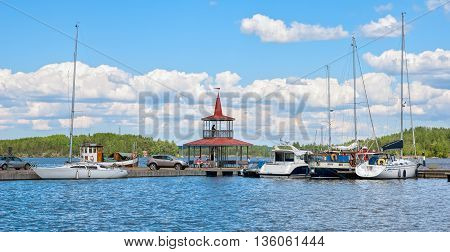 LAPPEENRANTA, FINLAND - JUNE 15, 2016: People sit on the benches near pavilion on the small pier with yachts and boats next to The Saimaa Lake