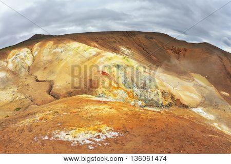 Unusual Iceland. Smoldering underground heat hillsides. In the hollows are last year's snow fields